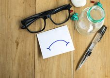 Paper with glasses and pens on wooden boards using business for emotion to bad stock image