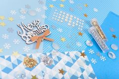 Paper and glitter for Christmas craft making. Paper, glitter and shiny accessories for Christmas craft making in white, blue and gold colors. Design for happy Royalty Free Stock Photography