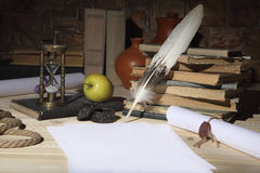Paper, goose feather, ink, hourglass and books on the desktop. Retro stylized photo. royalty free stock image