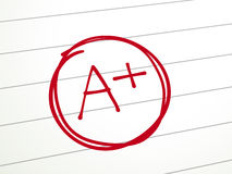 A paper is graded A Plus with red pen. Close up look at A Plus on lined paper with red pen Royalty Free Stock Images