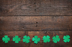 Paper green clover shamrock leaf border on dark wooden background. Space for copy, text, lettering royalty free stock images