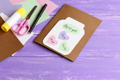 Paper greeting card with jar, colored hearts and wishes. Scissors, colored paper sheets, white cardboard, glue stick, black marker Stock Images