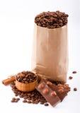 Paper hänger lös med kaffebönor och choklad. Arkivfoton