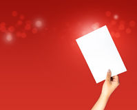 Paper hand holding on red background. Paper on arm and hand holding on red bokeh background, with copy space Royalty Free Stock Photography
