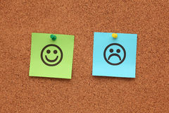 Paper with happy and sad faces on corkboard Stock Photography