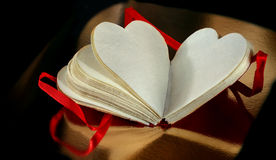 Paper heart. With hand-scooped paper and a ribbon on golden background, space for text stock image