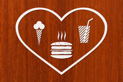 Paper heart with burger, beverage and icecream inside, abstract food concept Royalty Free Stock Photo