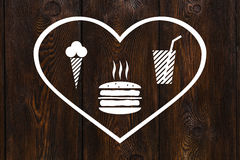 Paper heart with burger, beverage and icecream inside, abstract food concept Royalty Free Stock Image