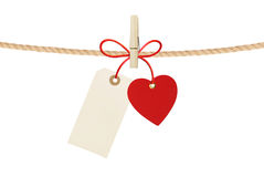 Paper heart and empty tag hang on cord isolated on white Royalty Free Stock Photo