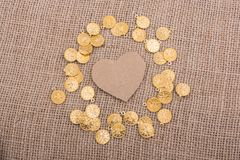 Paper heart with fake coins around it Stock Photography