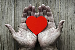 Paper heart in the hands of an elderly. Wooden background Royalty Free Stock Images