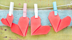 Paper heart hanging on the clothesline. On old wood background. Royalty Free Stock Image