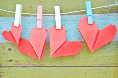 Paper heart hanging on the clothesline. On old wood background. Stock Photos