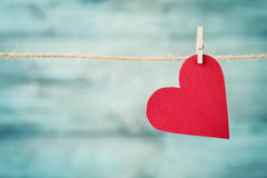 Paper heart hanging on string against turquoise wooden background for Valentines day