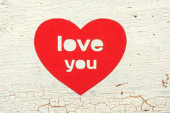 Paper heart on an old wooden door. Paper heart with the word love you on old wooden door Stock Photo