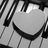 Paper heart on piano keyboard black and white Stock Photography
