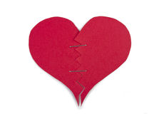 Paper heart repaired with staples. On white background Royalty Free Stock Images