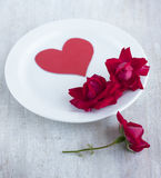 Paper heart and scarlet roses on the white round plate Stock Photography