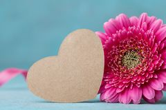 Paper heart tag and beautiful pink gerbera flower on turquoise table. Greeting card for Birthday, Woman or Mothers Day. royalty free stock photo