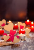 Paper hearts on clothespins  and burning candles on  wooden tabl Royalty Free Stock Photography