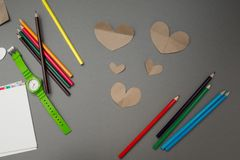 Paper hearts and colored pencils on a gray background stock images