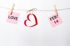 Paper hearts and LOVE and FEB. 14 hanging on the line on white background royalty free stock photography