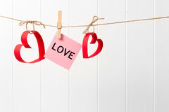 Paper hearts and LOVE hanging on the line on white background Royalty Free Stock Photo