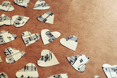 Paper hearts with music notes. On craft paper background with vintage tone Royalty Free Stock Image