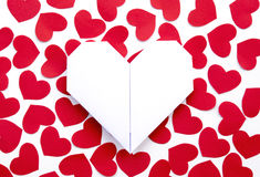 Paper Hearts on paper. Folding heart paper surrounding with some red heart paper on white paper Royalty Free Stock Images
