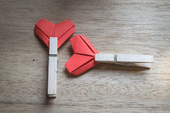 Paper hearts and wooden cloth pegs. On wooden background Royalty Free Stock Image