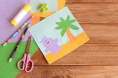 Paper hippo and palm tree applique, colored paper sheets, scissors, pencils, glue, eraser on wooden background with blank space Stock Photo