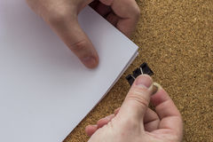 Paper holding. Paper in hand on background cork board Royalty Free Stock Photography