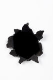 Paper hole. Black hole in white paper with black ragged edges Royalty Free Stock Photo