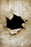 Paper Hole. Old crumpled paper sheet with ripped hole in the center Royalty Free Stock Photo