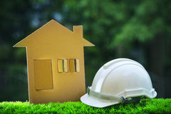 Paper home out line with safety helmet on green grass field wtih Stock Image
