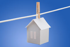 Paper house. On clothes line on a  blue background Royalty Free Stock Image