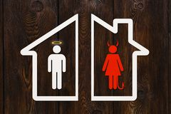 Paper house with angel man and devil woman. Divorce concept. Paper house with angel man and devil woman inside. Divorce concept. Abstract conceptual image royalty free stock images