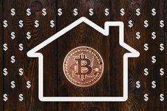 Paper house with bitcoin inside and rain of dollars. Abstract concept stock photo