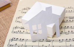 Paper house on a box a paper with musical notes Stock Image