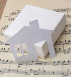 Paper house on a box a paper with musical notes Royalty Free Stock Images