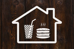 Paper house with burger and beverage inside, abstract food concept Stock Images