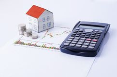 Paper house with coins and calculator on stock chart report stock image