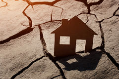 Paper house on cracked earth Stock Photos