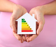Paper house with energy efficiency chart. Hands of woman holding paper house with energy efficiency chart royalty free stock photo