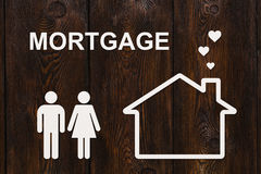 Paper house and family with mortgage text. Conceptual image Stock Photo