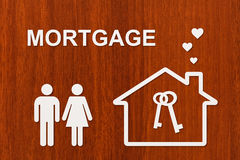 Paper house and family with mortgage text. Conceptual image Royalty Free Stock Image