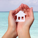 Paper House in Female Hands over Tropical Beach. Concept Stock Images