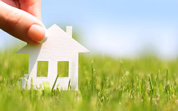 Paper house in green grass over blue sky. Concept of construction or mortgage. Eco Stock Image