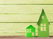Paper house on green wooden background Royalty Free Stock Photos