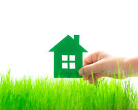 Paper house in hand. Over spring green grass. Real estate concept Stock Photos